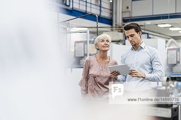 Businessman and senior woman with tablet talking in a factory