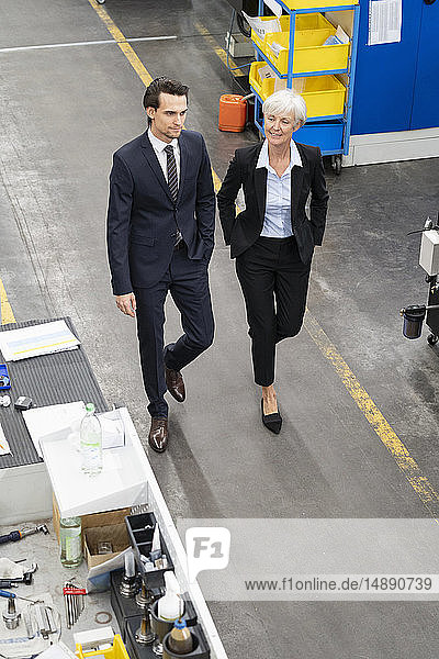 Businessman and senior businesswoman walking in a factory