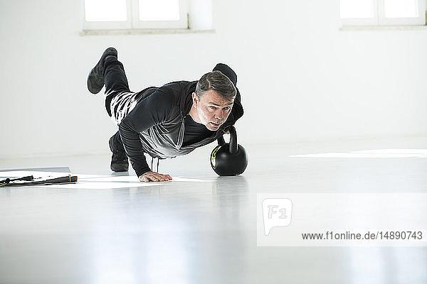 Mann macht sein Fitness-Regime  macht Kesselglocken-Liegestütze