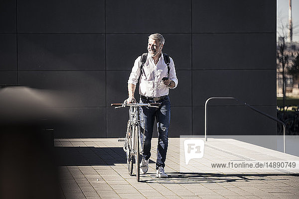 Smiling mature businessman with bicycle  cell phone and earphones on the go