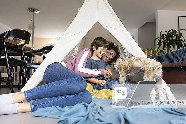 Mutter und Sohn liegen mit Hund im Spielzelt