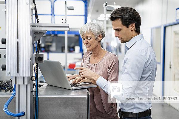 Geschäftsmann und leitende Geschäftsfrau  die in einer Fabrik am Laptop arbeiten