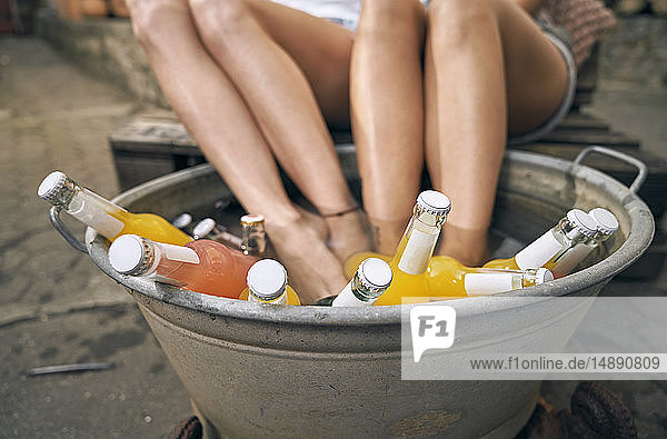 Friends relaxing in a backyard in summer  young women cooling their feet in a tub with drinks