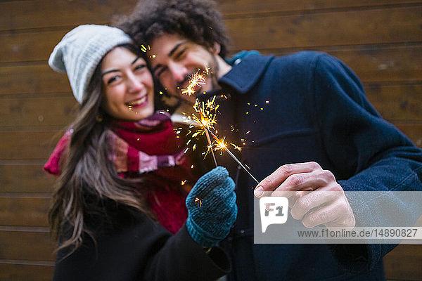 Glückliches junges Paar in Winterkleidung hält Wunderkerzen vor Holzwand