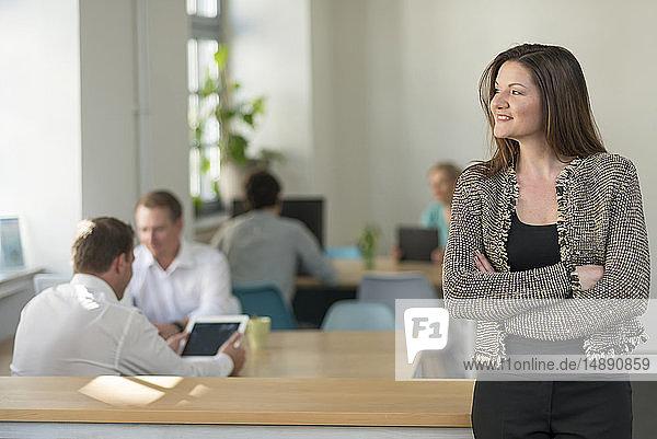 Lächelnde Geschäftsfrau im Büro mit Kollegen im Hintergrund