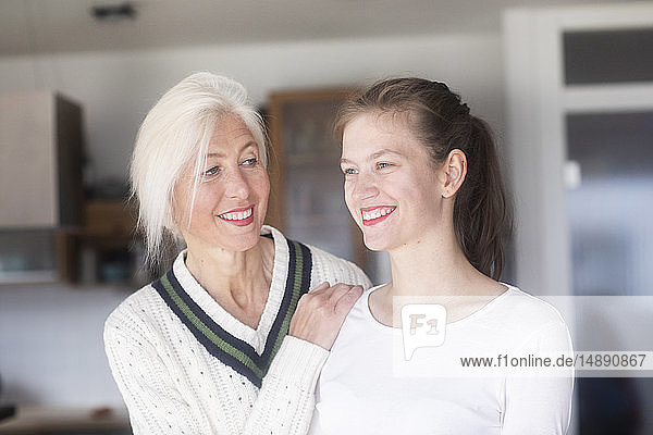 Portrait of smiling mature woman watching her adult daughter