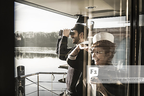 Kollegen  die auf einem Hausboot arbeiten und die Umgebung mit dem Fernglas beobachten