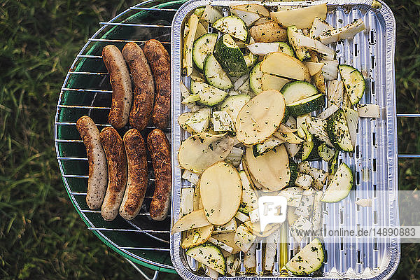 Grillen von Würsten und Gemüse auf einer Wiese
