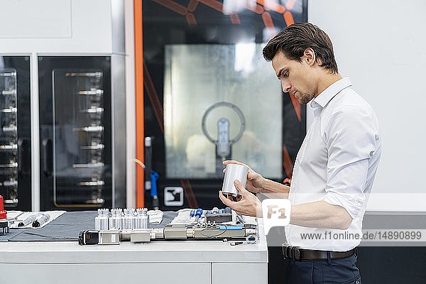 Businessman examining workpiece in a factory