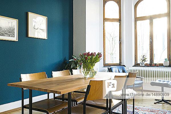 Holztisch und Stühle mit großer Fensterfront in modernem Wohnzimmer in stilvoller Wohnung