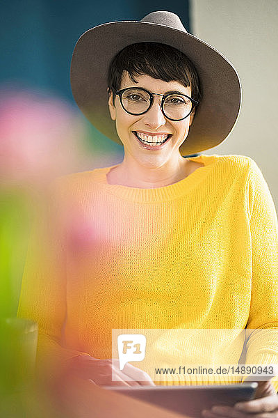 Portrait of happy stylish woman holding tablet