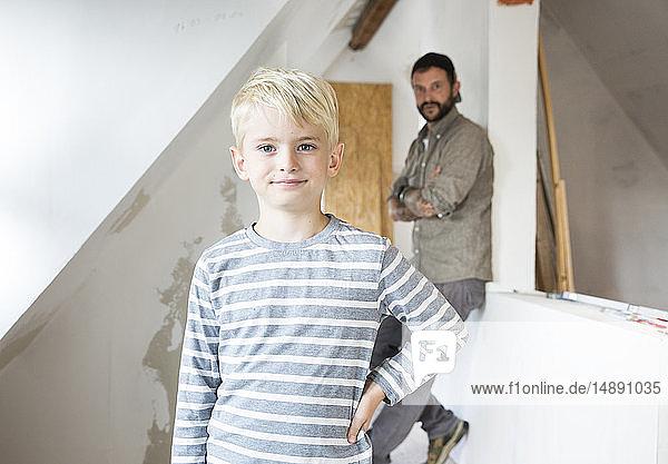 Porträt eines selbstbewussten Jungen  der mit seinem Vater beim Dachbodenausbau arbeitet