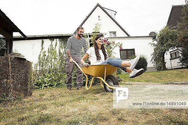 Verspielter Mann schiebt Frau in Schubkarre sitzend im Garten