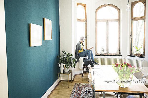 Frau sitzt auf dem Fensterbrett in stilvoller Wohnung  hält Kaffeetasse und liest ein Buch