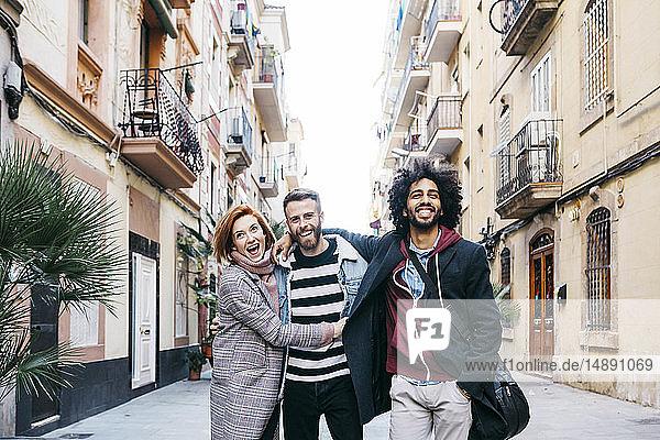Drei glückliche Freunde spazieren in der Stadt