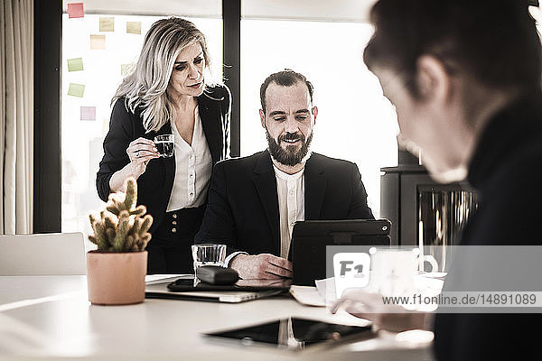 Business people working together in office,  businesswoman watching colleague,  looking over shoulder