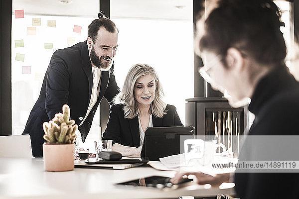 Geschäftsleute  die im Büro zusammenarbeiten  Geschäftsmann  der seinen Kollegen beobachtet und über die Schulter schaut