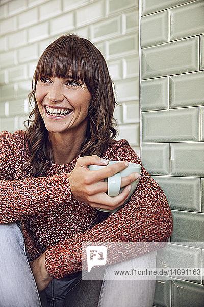 Glückliche Frau sitzt in der Küche und trinkt Tee