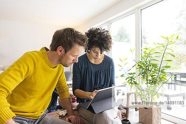 Paar  das im Wohnzimmer sitzt und ein digitales Tablett benutzt
