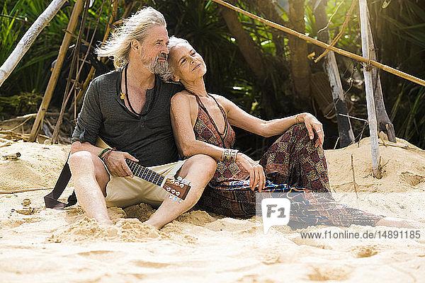 Porträt eines glücklichen älteren Hippie-Paares mit Gitarre beim Entspannen am Strand