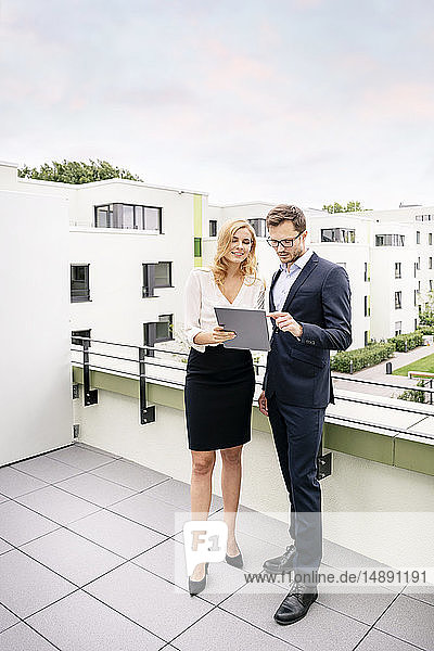 Real estate agent standing on a balcony with customer  looking at digital tablet