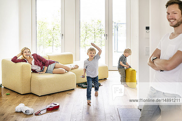 Happy family moving into their new home  parents playing with their kids