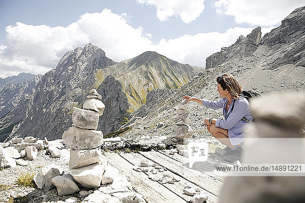 Austria  Tyrol  woman on a hiking trip in the mountains building up a cairn