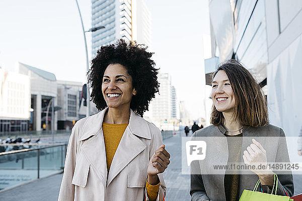 Zwei glückliche Frauen mit Einkaufstaschen in der Stadt
