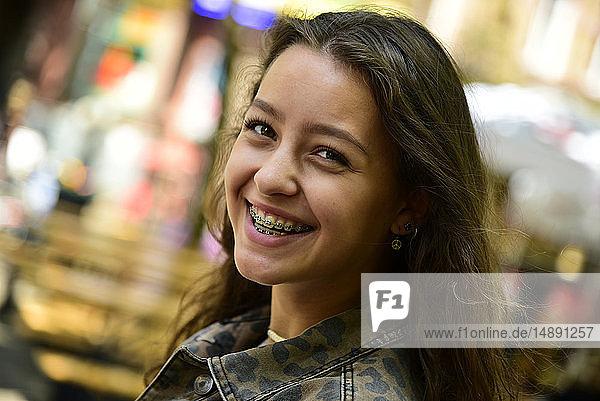 Porträt einer lachenden Teenagerin mit Zahnspange
