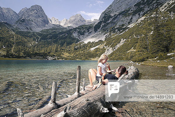 Austria  Tyrol  playful mother and daughter on tree trunk at lake Seebensee