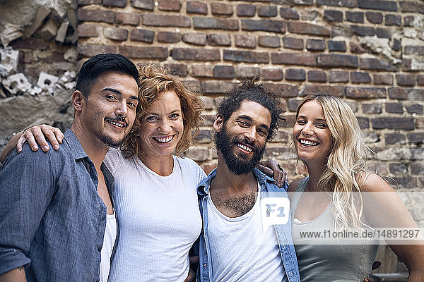 Four friends standing in front of brick wall  with arms around