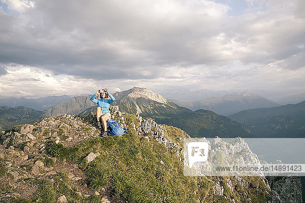 Österreich  Tirol  Frau auf Wanderung in den Bergen mit Handyfoto auf dem Gipfel