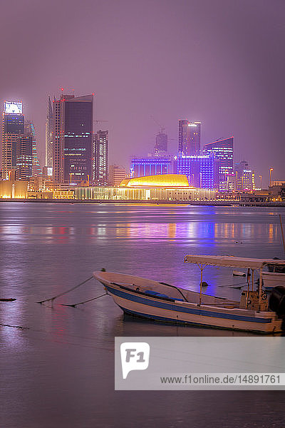Moored motorboat by city skyline at night in Manama  Bahrain