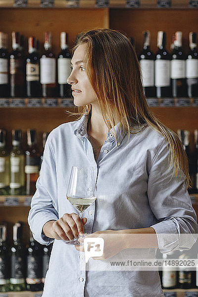Young woman holding glass of white wine