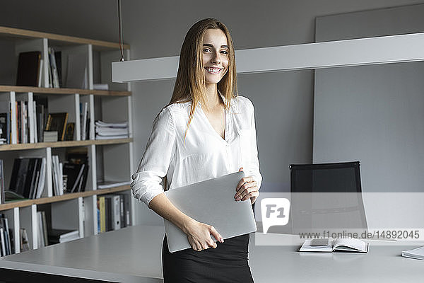 Young businesswoman holding laptop in office