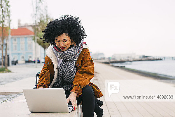 Young woman using laptop on waterfront in Lisbon  Portugal