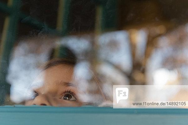 Girl peering through window