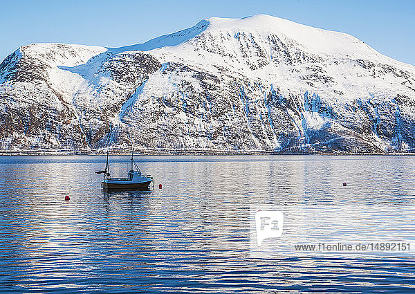 Fishing boat by snow covered mountain in Tromso  Norway