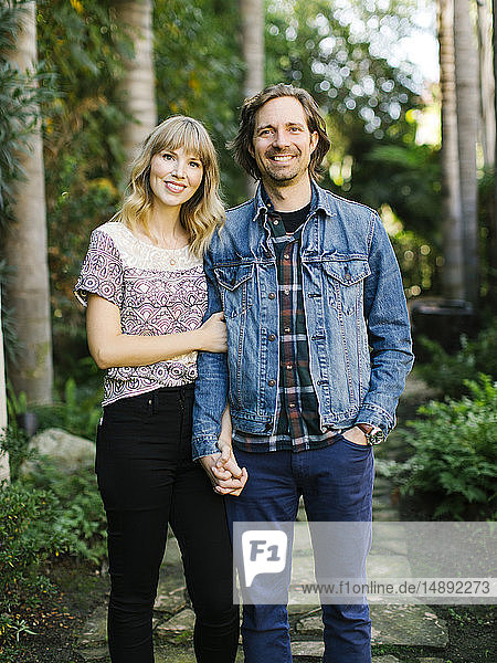 Mid adult couple holding hands in garden