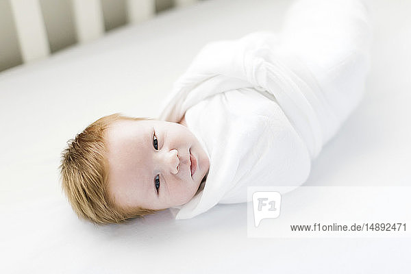 Swaddled baby boy in cot