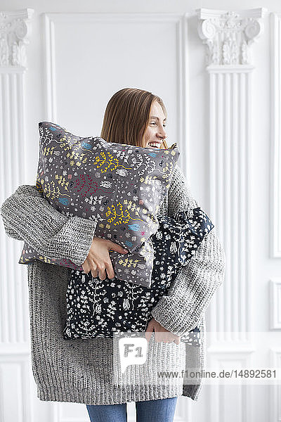 Smiling woman holding patterned cushions