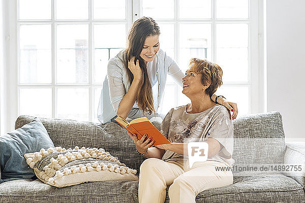 Mother and adult daughter looking at book on sofa