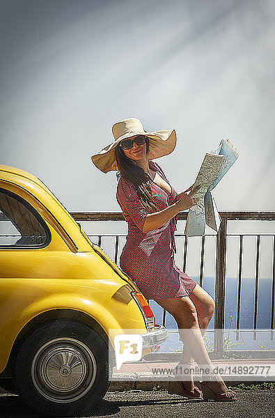Woman holding map leaning on yellow car