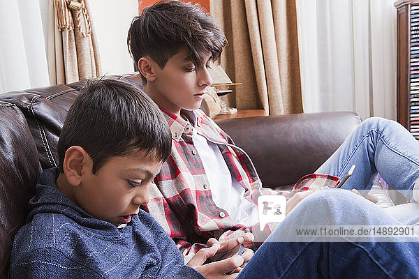 Brothers using smart phones on sofa