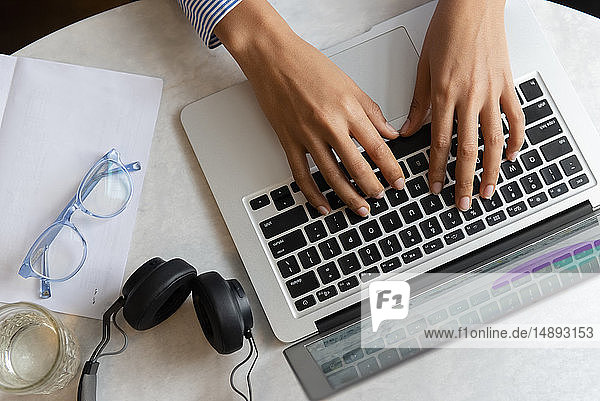 High angle view of young woman's hands typing on laptop
