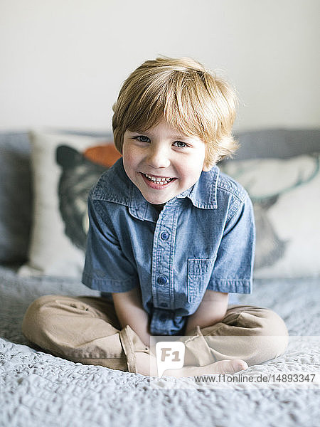 Smiling boy sitting on bed