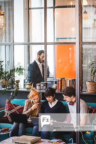 Zuversichtliche Kollegen diskutieren am Laptop gegen Geschäftsmann im Kreativbüro