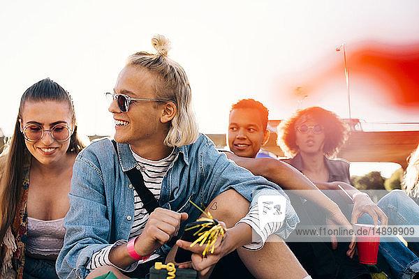 Glückliche Freunde sitzen bei sonnigen Tagen bei einer Veranstaltung vor klarem Himmel