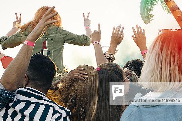 Rückansicht von begeisterten Fans  die an sonnigen Tagen ein Musikkonzert genießen