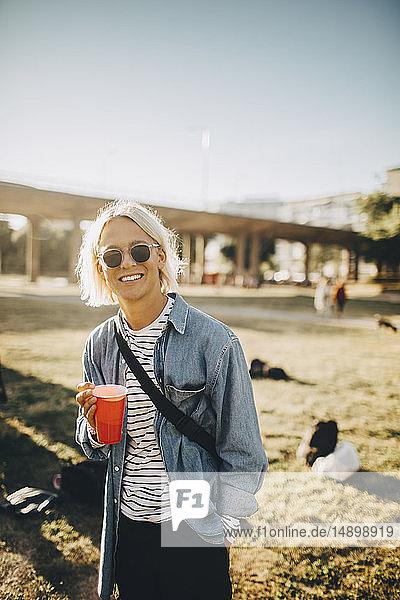 Porträt eines lächelnden jungen Mannes  der während eines Konzerts auf dem Rasen steht und etwas trinkt